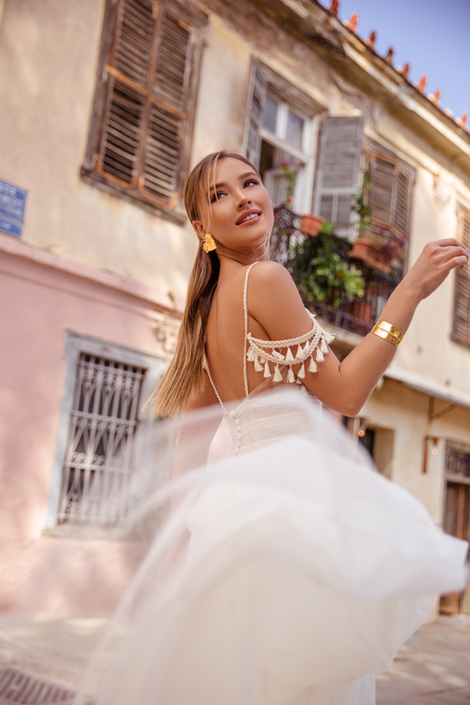 Τούλινη φούστα νυφικού σε αέρινη κίνηση και κοσμήματα thallo με φόντο γραφικό νεοκλασικό